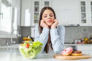 girl chooses between donuts and vegetable salad