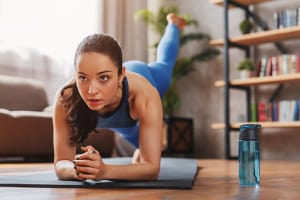 Fit young woman wearing sportswear working out at home