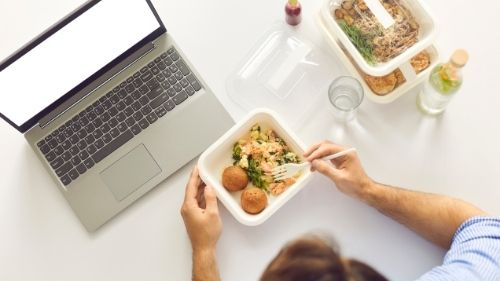 man eating packed lunch at desk
